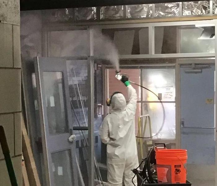 man wearing ppe cleaning
