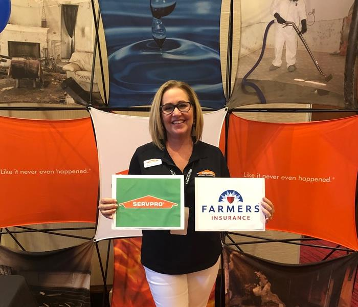 woman holding SERVPRO and Farmers Insurance signs