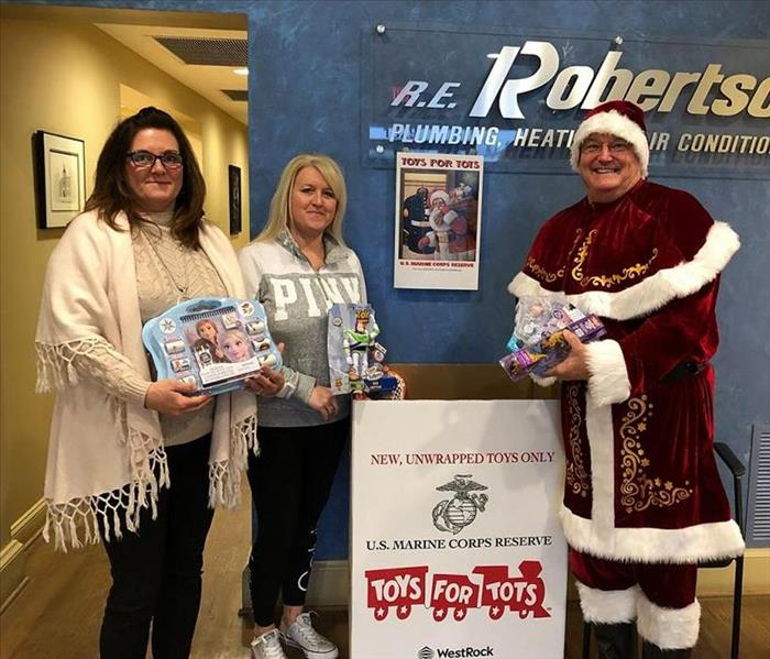 Santa and 2 ladies holding toys with Toys for Tots