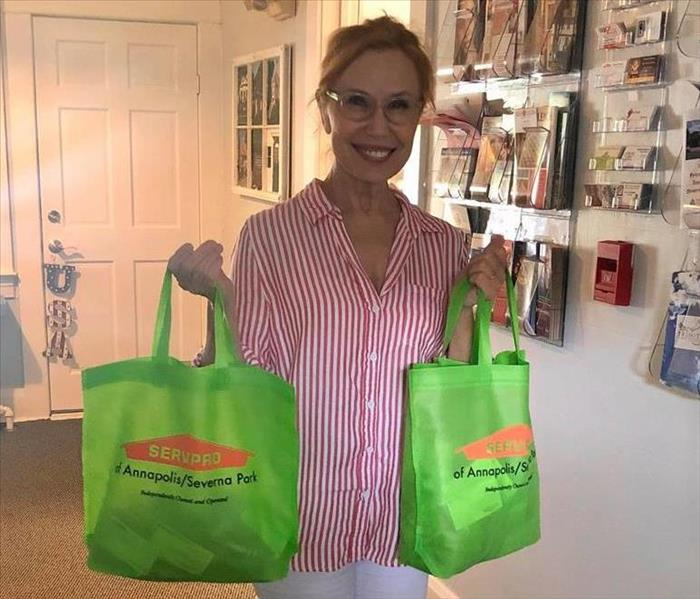 Liz CEO of the Chamber of Commerce holding canvas goodie bags