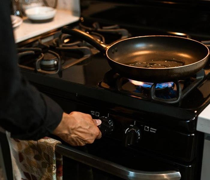 woman lighting a gas stove